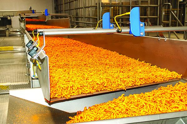 Cheetos snacks move through an accumulation conveyor at the Perry, GA, Frito-Lay manufacturing facility.